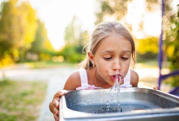 Веселая чудесная девочка пьет прохладную пресную воду из небольшого фонтана в летнем теплом солнечном парке на долгожданных каникулах