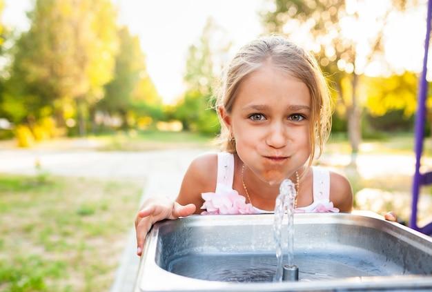 명랑 멋진 소녀는 오랫동안 기다려온 휴가에 여름 따뜻한 화창한 공원에서 작은 분수에서 시원한 신선한 물을 마신다
