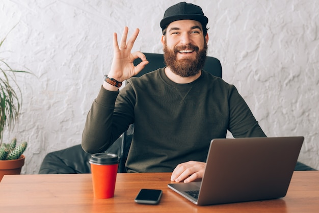 Cheerful worker sitting in office and showing ok gesture