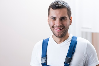 Cheerful workman at white wall