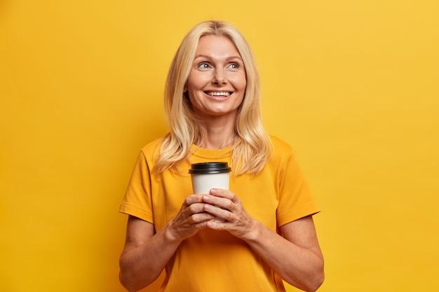 化粧をした陽気なしわのある金髪の女性は、休暇の計画を持っていますカジュアルな黄色のtシャツのポーズに身を包んだテイクアウトのコーヒーを飲みながら、屋内で家族のことを考えています。人々の年齢と余暇の概念