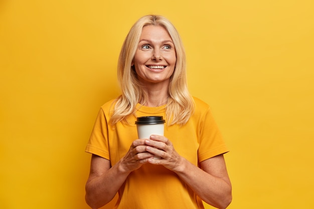 Cheerful wrinkled blonde woman with makeup has plans for vacation enjoys drinking take away coffee dressed in casual yellow t shirt poses indoor thinks about family. people age and spare time concept