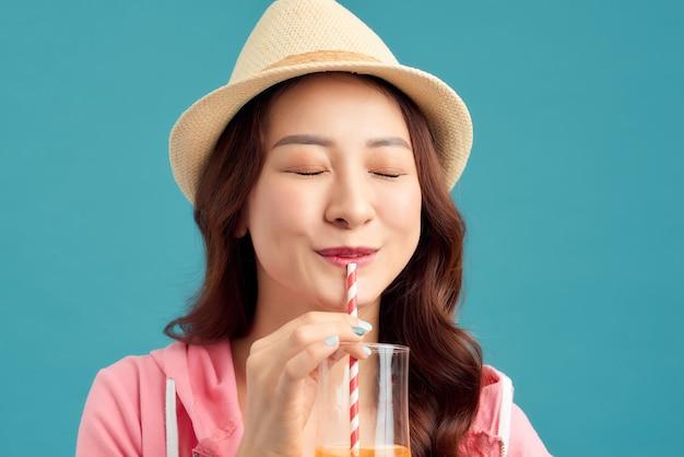 과일 주스를 마시고 밀짚 모자, 흰색 티셔츠, 짧은 청바지, 파란색 배경 위에 분홍색 재킷을 입은 쾌활한 아시아 여성.