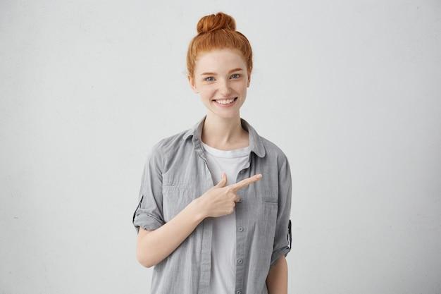 Веселая кавказская женщина с веснушками и пучком рыжих волос широко улыбается и указывает боком указательным пальцем на пустую белую стену с копией пространства, указывая на некоторую интересную информацию
