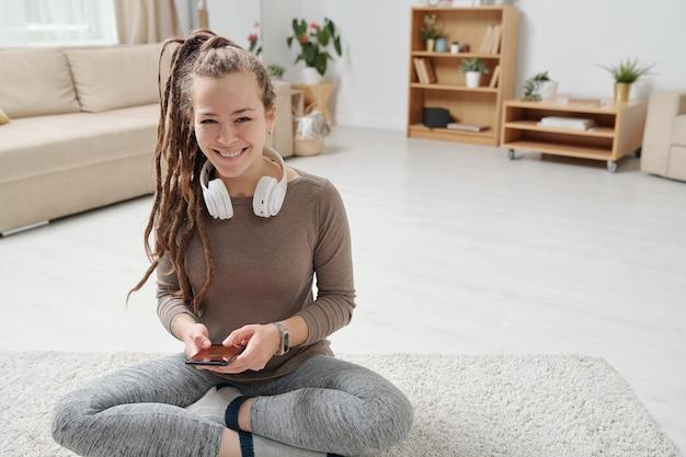 가정 환경에서 요가를 연습하는 동안 스마트 폰을 사용하는 헤드폰으로 쾌활한 젊은 활동적인 여자