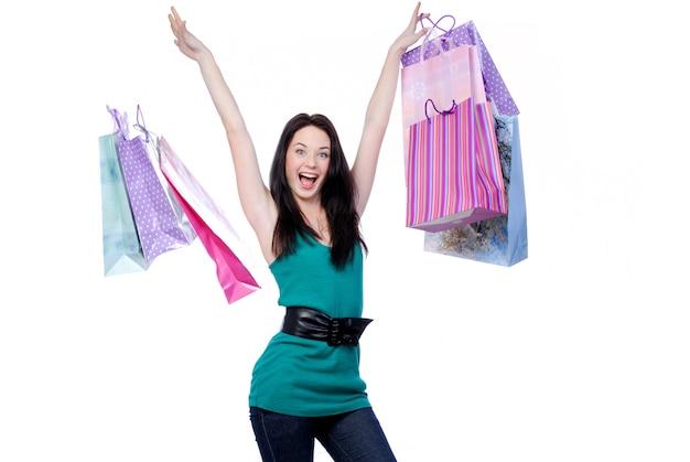 Веселая молодая взрослая девушка бросает цветные сумки