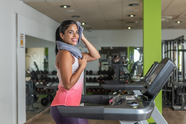 Cheerful young adult woman looking at camera wiping face with towel while using a treadmill at gym.