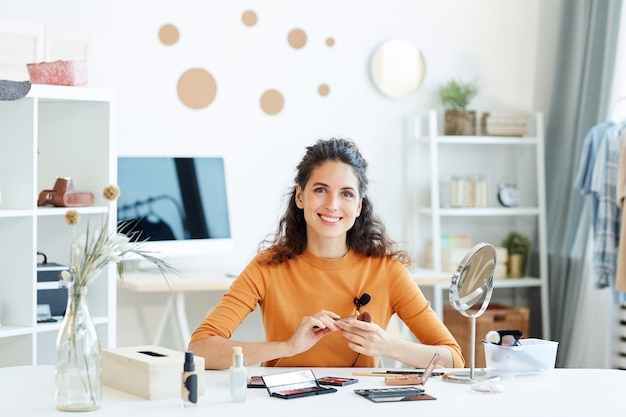 Cheerful young adult woman sitting at table with beauty products on it looking smiling