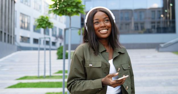 街の通りで元気に笑って、スマートフォンで音楽を聴いてヘッドフォンで陽気な若いアフリカ系アメリカ人の美しい女性。携帯電話のプレーヤーで歌を楽しんでいるかなり幸せな女性。