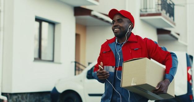 Веселый молодой афроамериканец доставщик в красной форме, вынимая картонную коробку из фургона и ходить к дому во время прослушивания музыки в наушниках и улыбается. открытый.