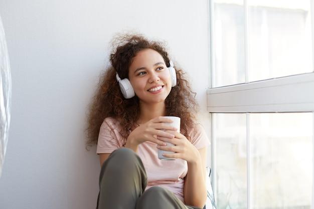 巻き毛の陽気な若いアフリカ系アメリカ人女性が窓際に座って、ヘッドフォンでお気に入りの音楽を聴き、お茶を飲み、窓を見て、家で一日を楽しんでいます。