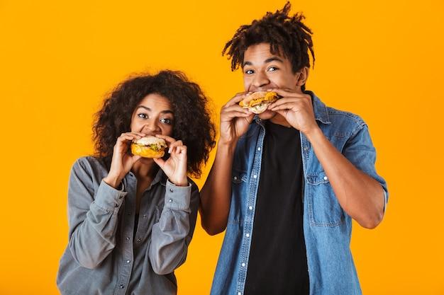 孤立して立って、ハンバーガーを食べて陽気な若いアフリカのカップル