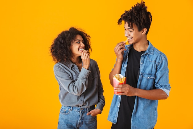 Cheerful young african couple standing isolated, eating french fries