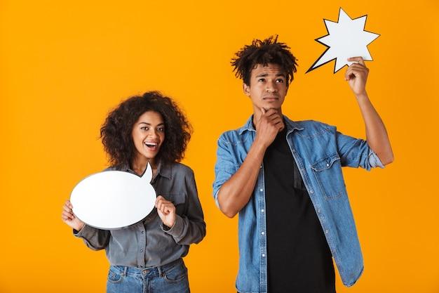 Веселая молодая африканская пара стоя изолированно, держа пустые пузыри речи