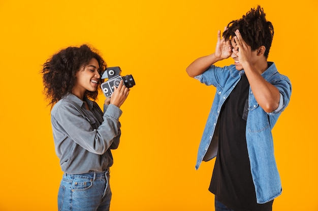 Cheerful young african couple standing isolated, making a video with camera