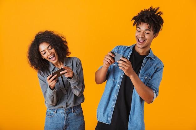 Веселая молодая африканская пара стоя изолированно, играя в игры на мобильном телефоне