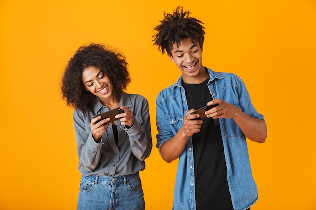 Cheerful young african couple standing isolated, playing games in mobile phone