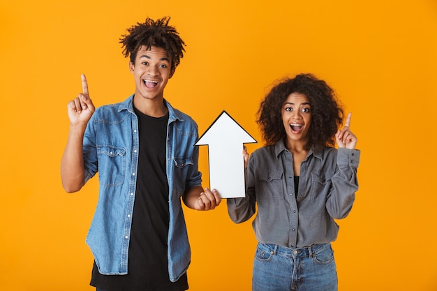 Cheerful young african couple standing isolated, pointing arrow up
