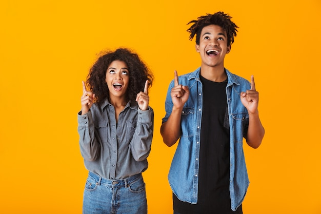 Cheerful young african couple standing isolated, pointing fingers up