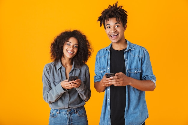 Cheerful young african couple standing isolated, using mobile phones