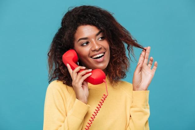 Giovane signora africana allegra che parla per telefono.