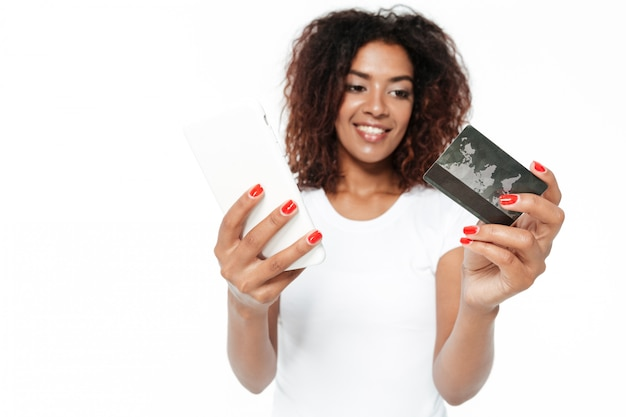 Cheerful young african lady using phone holding credit card.