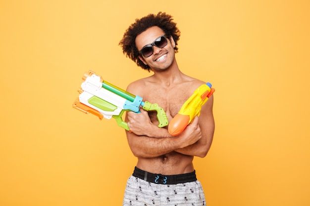 Cheerful young african man holding toy water gun.