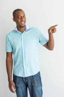 カジュアルな服を着て、カメラを見ている朗らかな若いアフリカの男。