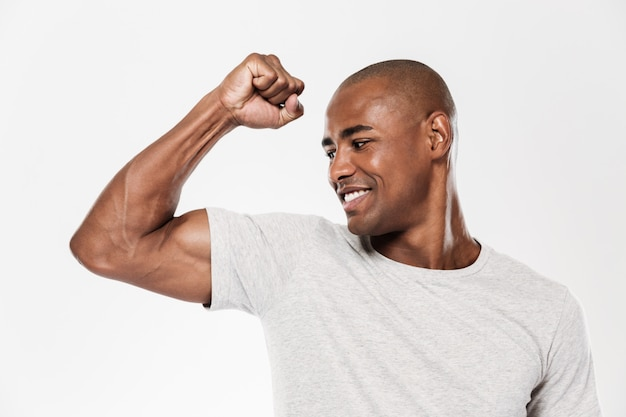 Cheerful young african man showing biceps.