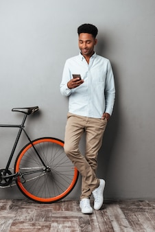 Cheerful young african man standing over grey wall chatting