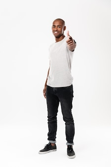 Cheerful young african man standing isolated