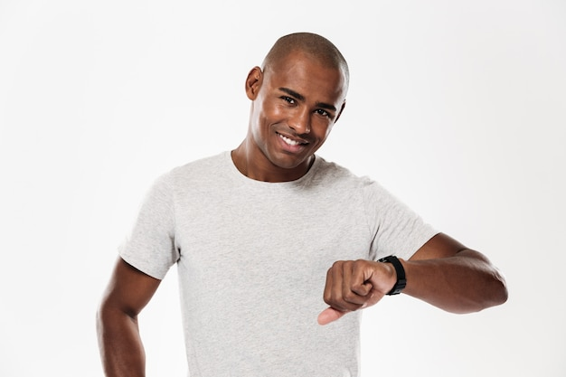 Cheerful young african man using watch.