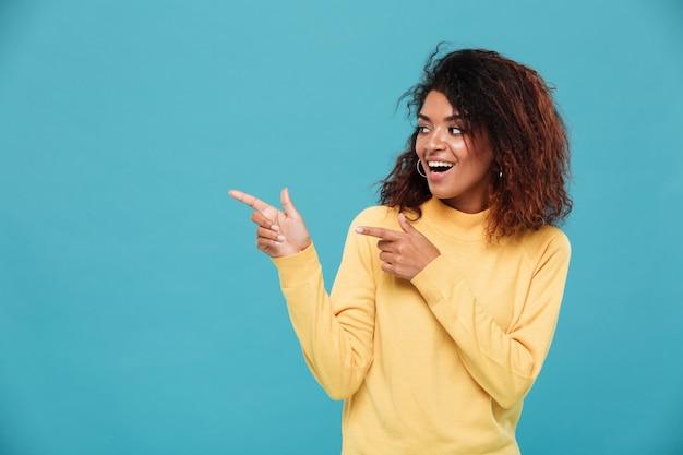따뜻한 스웨터를 입은 쾌활한 젊은 아프리카 여성