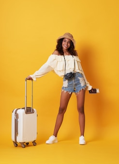 Cheerful young african woman dressed in summer clothes holding passport with money