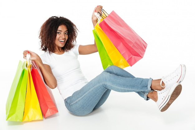 Cheerful young african woman holding shopping bags.