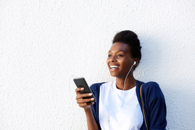 Cheerful young african woman listening music on smart phone