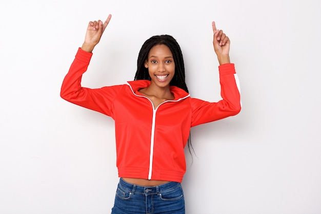 Cheerful young african woman pointing fingers up on white background