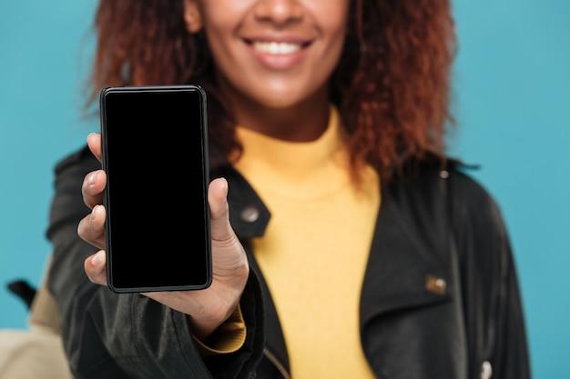 携帯電話の表示を示す陽気な若いアフリカ人女性。