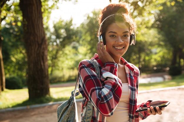電話でおしゃべりを歩いている陽気な若いアフリカ人女性。
