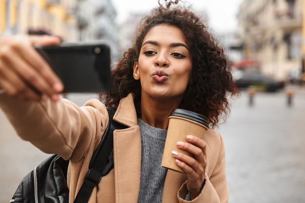 コートを着て屋外を歩く、持ち帰り用のコーヒーカップを持って、自分撮りをする陽気な若いアフリカの女性