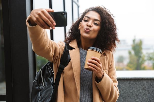 Веселая молодая африканская женщина в пальто гуляет на свежем воздухе, держит чашку кофе на вынос, делает селфи