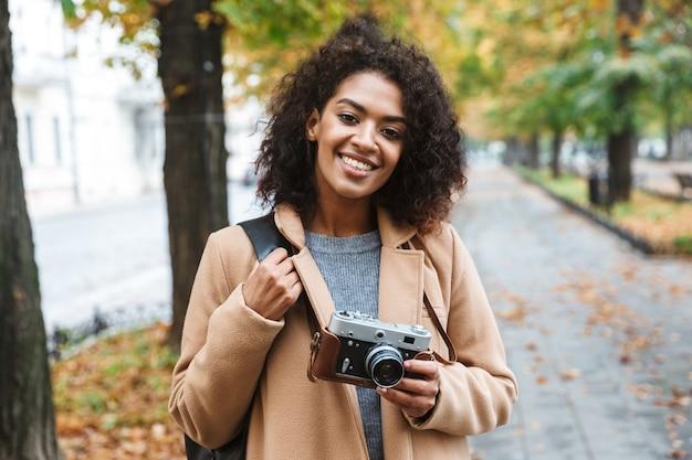 야외에서 걷고 코트를 입고 쾌활 한 젊은 아프리카 여성