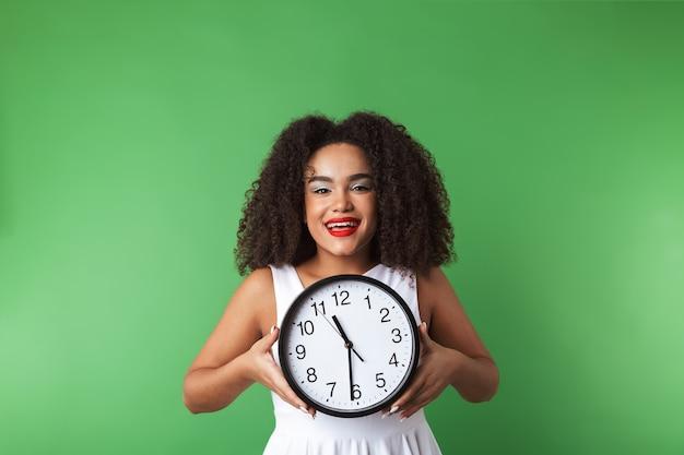 Веселая молодая африканская женщина в платье стоит изолированно, показывая настенные часы
