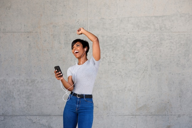 Cheerful young african woman with earphones and mobile phone listening to music