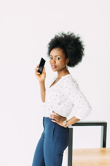 Cheerful young afro american business woman talking on cell phone, standing near the modern chair, isolated on white