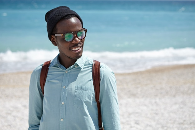 Cheerful young afro american male student wearing eyeglasses and hat carrying knapsack on his shoulders spending leisure time after college by the sea, having nice walk along desert pebble beach