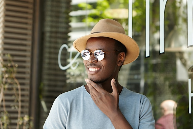 Cheerful young afro american male in trendy sunglasses and headwear touching his chin and smiling happily as he sees his friend approaching him while waiting for lunch at sidewalk restaurant