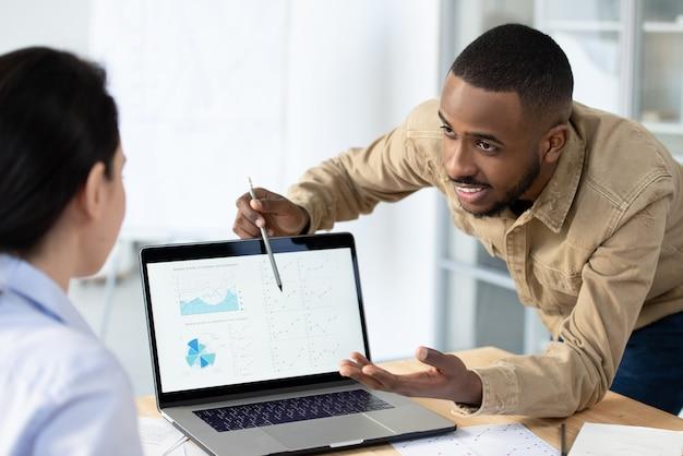 ビジネスソリューションを提供しながらラップトップ上のオンライングラフを指している陽気な若いアフリカ系アメリカ人のマネージャー