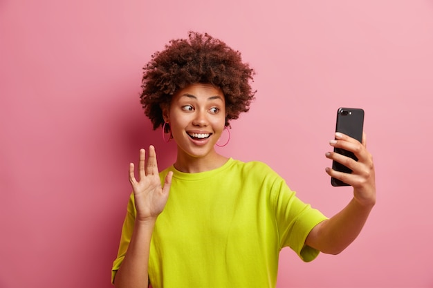 Cheerful young afro american woman with cury hair waves in smartphone camera makes hi gesture while having video conference talks to best friend on distance wears casual t shirt poses indoor