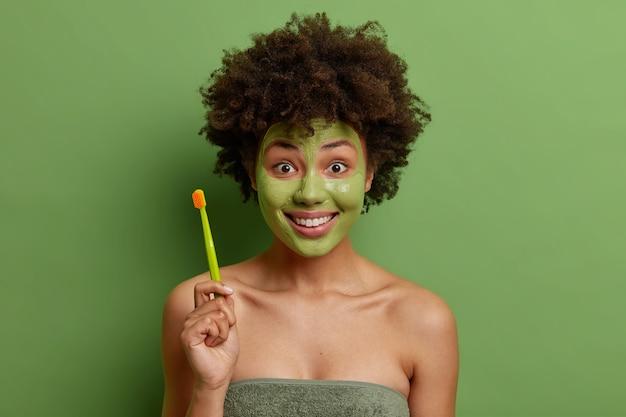 タオルに包まれた陽気な若いアフリカ系アメリカ人女性は、朝の日課を行うために歯ブラシを保持し、鮮やかな緑の壁の上に分離された栄養のある顔のマスクを適用します